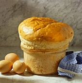 Bread in shape of souffle in souffle dish, a few eggs beside it