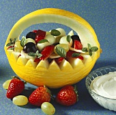 Melon baskets with fruit salad and mint; whipped cream