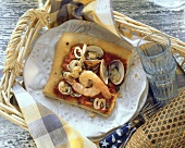 A piece of seafood pizza on plate in wicker tray