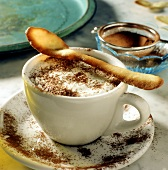 Cappuccino ice cream in coffee cup with biscuit spoon