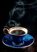 Dampfender schwarzer Kaffee in blauer Tasse mit Goldrand