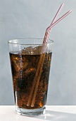 Cola in glass with ice cubes and two straws