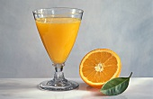A glass of orange juice, half an orange and a leaf