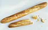 Ganzes & halbes Baguette & einige abgebrochene Brotstücke