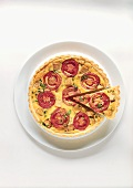 Quiche with tomatoes and soya meat, one piece cut out