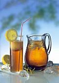 Glass of iced tea with ice cream, lemon, straw & jug of tea