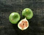Zwei ganze grüne Feigen & eine halbierte Feige