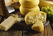 Zwei Käsesorten(Laibe,Stücke) & Käsereibe mit geriebenem Käse