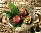 Drei Mangostanen mit Blättern in Schale,daneben eine einzelne