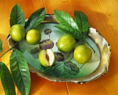 Jujube fruit, one cut open, with leaves on tray