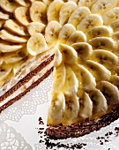 Banana gateau with banana slices & flaky chocolate edge