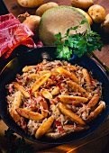 Fried potato noodles with bacon and sauerkraut in the pan