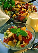 Mixed fruit salad with nuts and mint leaf