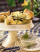Courgette quiche (one piece on server) with herb sauce