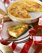 Quiche Lorraine in baking dish and a piece with chives