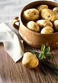 Potatoes in earthenware pot & single potatoes with herbs