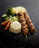 Souvlaki with rice & salad garnish on dark background