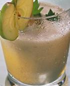 Sellerie-Apfel-Drink mit Apfelscheibe auf Glasrand