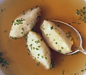 Semolina dumplings (detail) with spoon in broth with chives
