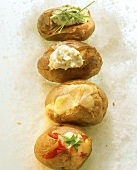 Baked potatoes with various fillings on bed of salt
