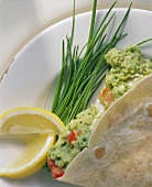 Tortilla with guacamole, chives and lemon wedges