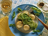 Polenta dumplings with pesto and basil leaves