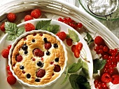 Berry clafoutis in souffle dish with raspberries, redcurrants