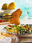 Viennese fried chicken (Backhendl) piece on fork, & corn salad