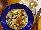Duck legs on bed of vegetables with cream sauce