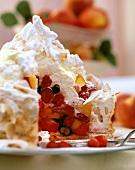 Coconut meringue gateau with summer fruit on plate