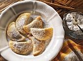 Plum pasties (Powidltascherln) with icing sugar on white plate
