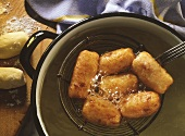 Grandma's croquettes, on ladle above hot oil