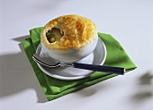 Clear vegetable broth with puff pastry topping in soup bowl