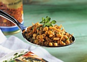 Lentil salad with carrots and herbs on spoon