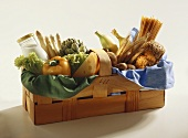 Bread, pasta, bananas, vegetables, milk & cheese in basket