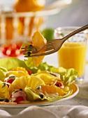 Salat mit Ananas, Orangen & Tomaten auf Teller & Gabel