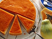 Almond and papaya cake, pieces cut, on glass plate