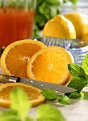 Orange, partly sliced, with knife, mint