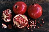 Granatäpfel, ganz, halbiert und Granatapfelkerne