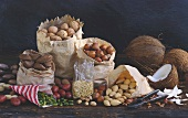 Nuts in various paper bags & coconuts on wooden background