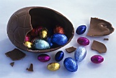 Chocolate egg, opened, with small coloured Easter eggs inside
