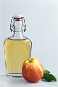 A bottle of apple vinegar and an apple
