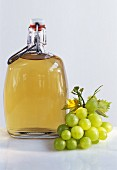 A bottle of grape vinegar, green grapes beside it