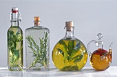 Four different oil bottles with herbs and spices