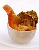 Various dried fruits in white plastic bowl