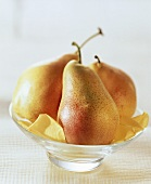 Three whole yellow & red pears on rose petals in glass bowl