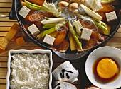 Sukiyaki in pan, egg yolk in soy sauce and rice