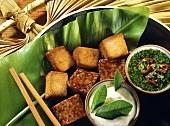 Tofu & tempeh fondue on banana leaf with coriander sauce