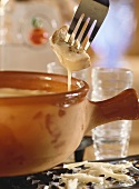 Vaudois fondue with piece of bread on fork above fondue pot