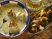Bier-Käse-Fondue mit Brezenstückchen auf Gabeln und im Korb